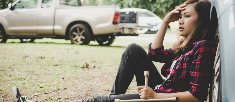 Woman sitting beside car with flat tyre looking frustrated