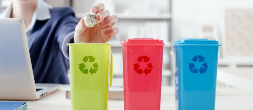 Three mini recycling bins on a desk at work