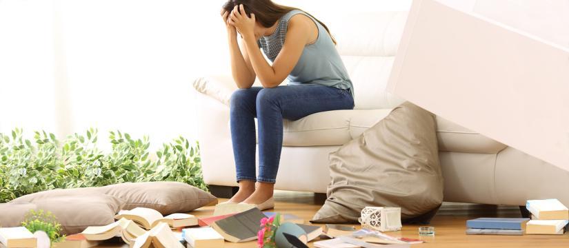 Woman sitting head in hands in apartment that's been broken into