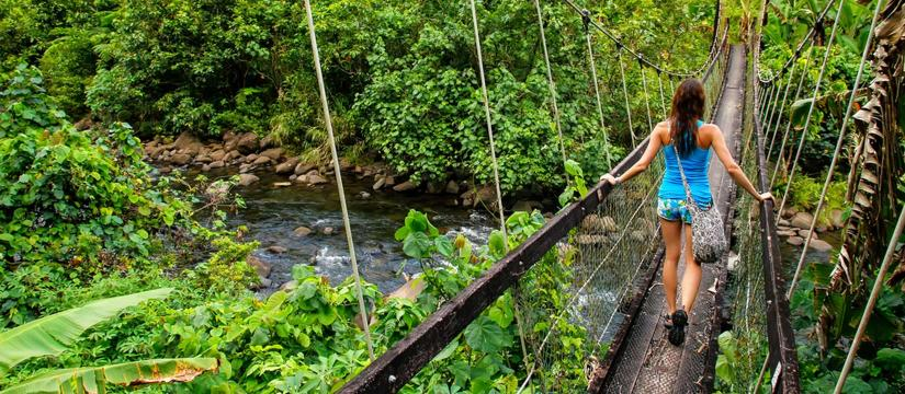 Woman crossing walking bridge in rainforest