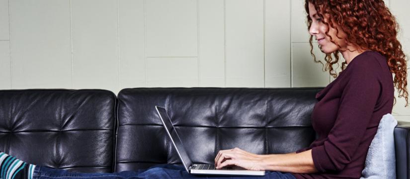 Woman working on computer on sofa