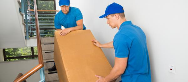 Two removal men lifting boxes upstairs