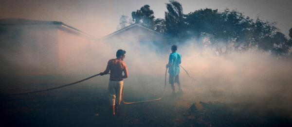 Shot of two people trying to fight a bush fire threatening a house