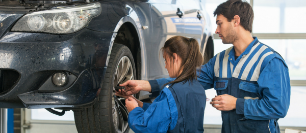 Car mechanic working with young female apprentice.